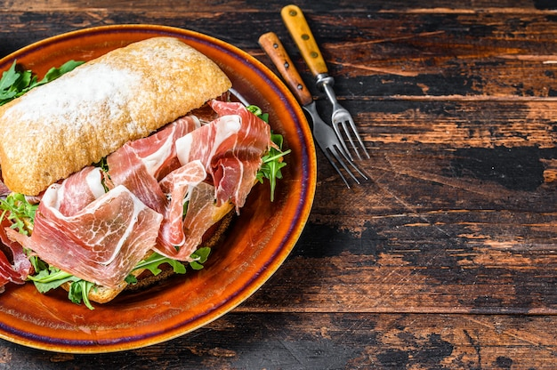 Spanish bocadillo de jamon, serrano ham sandwich on ciabatta bread with arugula. dark wooden table. top view. copy space.
