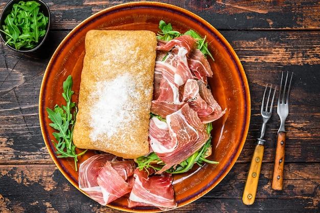 Испанский бокадильо де хамон, сэндвич с ветчиной серрано на хлебе чиабатта с рукколой. темный деревянный стол. вид сверху.