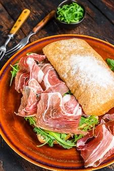 Испанский бокадильо де хамон, сэндвич с ветчиной серрано на хлебе чиабатта с рукколой.