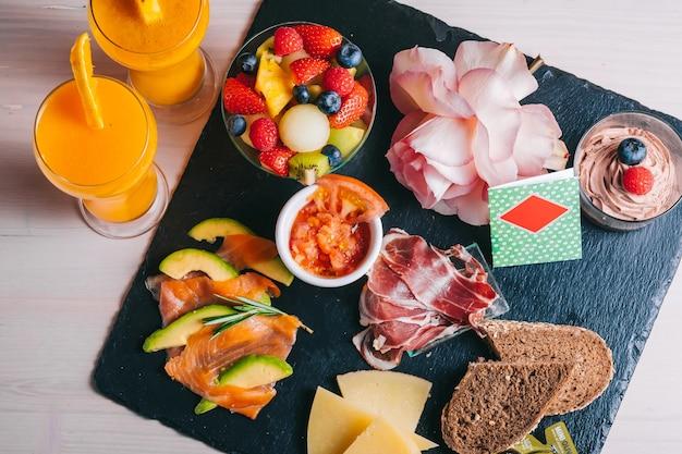 黒いプレートにオレンジジュースサーモンとイベリコハム、チーズ、トマトをセットしたスペインの朝食。上面図