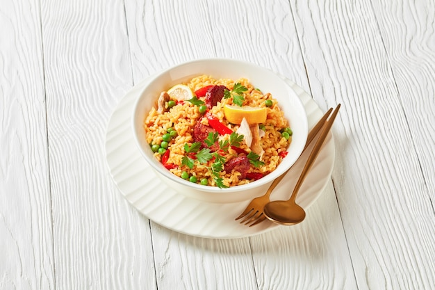 Spanish chicken paella with valencian bomba rice, chicken thigh meat, chorizo sausages, vegetables and spices served on a white plate on a white wooden table