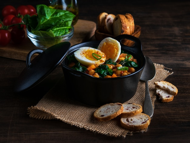 Spanish chickpea and spinach stew with eggs on rustic wooden background. spanish cuisine.