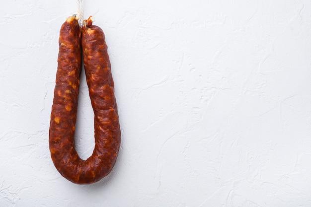 Испанская колбаса чоризо на белом фоне, вид сверху с пространством для текста.