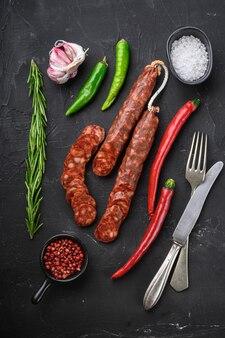Ломтики испанской колбасы чоризо с травами и специями на черной текстурированной поверхности, вид сверху.