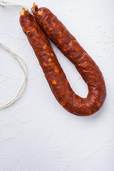 Spanish chorizo sausage on white table.