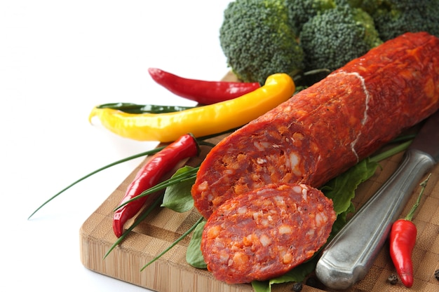 Spanish chorizo sausage with chili peppers and broccoli on a wooden board