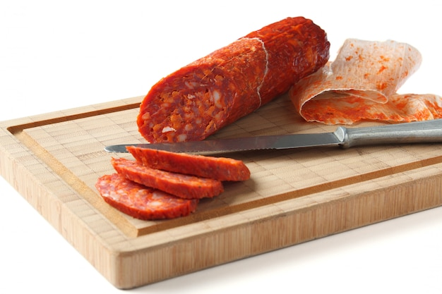 Spanish chorizo sausage with knife on wooden board, focus is on sausage