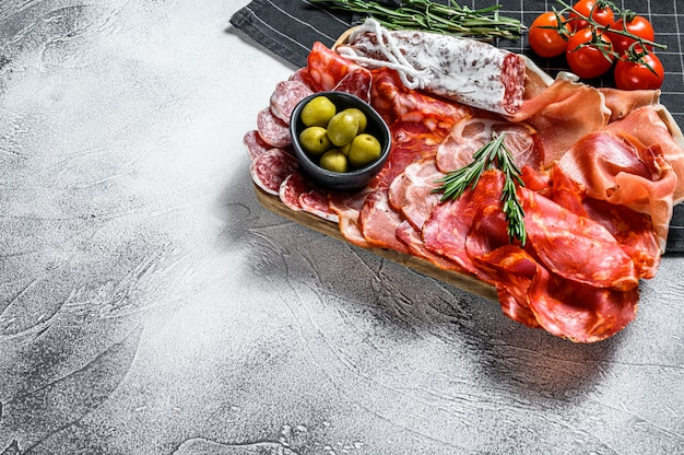Spanish cold meat assortment. chorizo, fuet,loin,  jamon iberico, olives. gray surface. top view. copy space