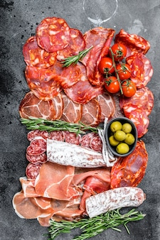 Spanish cold meat assortment. chorizo, fuet, lomo, jamon iberico, olives. black background. top view.