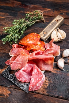 Spanish cured meat  salami, jamon, choriso cured sausages on a meat cleaver. dark wooden background. top view.