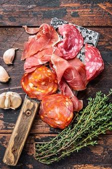 スペインの塩漬け肉サラミ、ハモン、チョリソ塩漬けソーセージを肉切り包丁で。暗い木の背景。上面図。