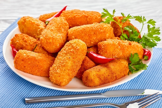 Spanish deep-fried golden brown potato croquettes, croquetas on a white plate on a wooden table with fork and knife