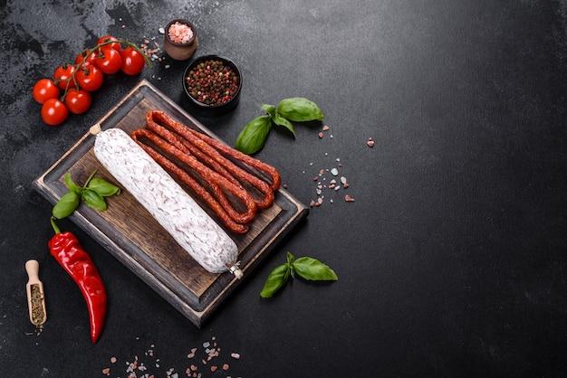 Испанская сушеная колбаса салями на темном фоне бетона. приготовление вкусных свежих бутербродов