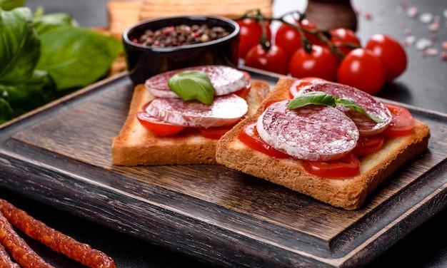 어두운 콘크리트 배경에 스페인식 말린 소시지 살라미 소시지. 맛있는 신선한 샌드위치의 준비