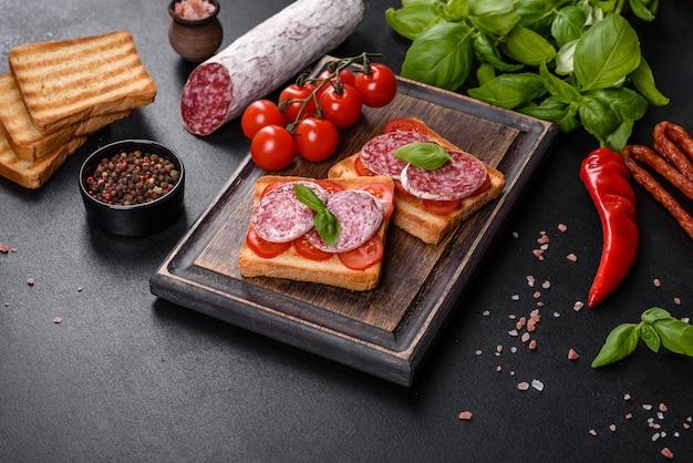 어두운 콘크리트 배경에 스페인 말린 소시지 살라미 소시지. 맛있는 신선한 샌드위치 준비