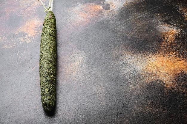 Испанский сухой салями fuet в травах на темном фоне, плоская планировка с копией пространства.