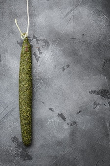 Spanish dry salami sausage fuet in herbs on grey background with space for text.