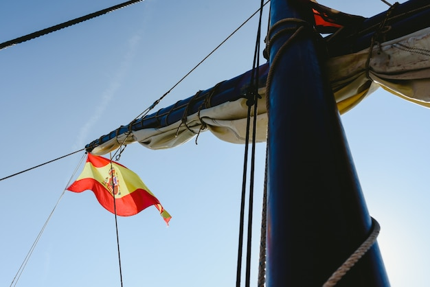 Spanish flag on commercial sailing ship.