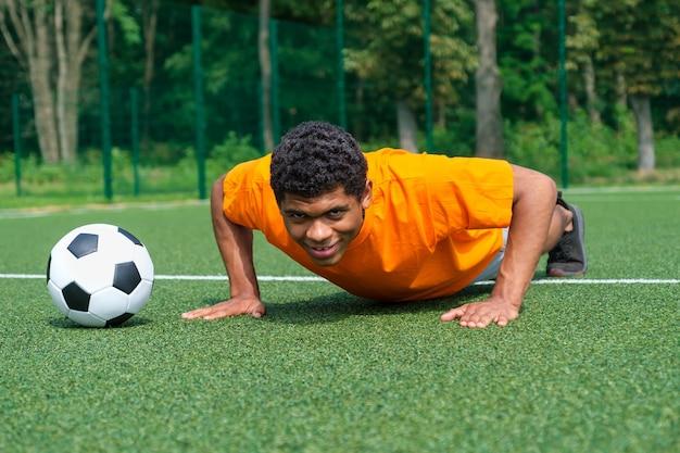 Испанский футболист летом разминается на тренировке на спортивной площадке