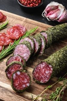 Ломтики испанской колбасы салями fuet на фоне balck.
