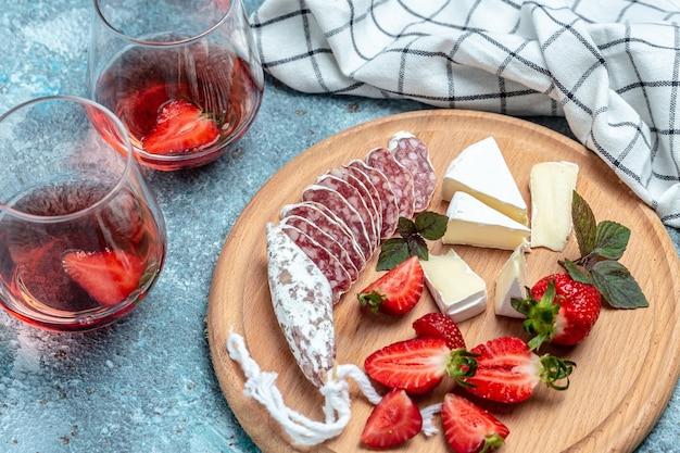 スペインのフエサラミとカマンベールチーズ、イチゴ。食品レシピの背景。閉じる。
