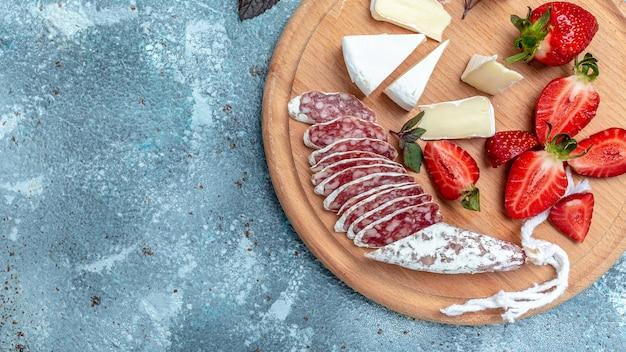 スペインのフエサラミとカマンベールチーズ、イチゴ。長いバナー形式。上面図。