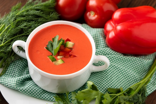 Spanish gazpacho soup on a wooden background with tomatoes and herbs.