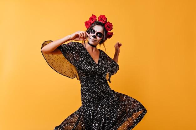 Испанская девушка в черном шифоновом платье танцует народный танец и улыбается. фото женщины в полный рост с фейс-артом и красными розами в волосах.