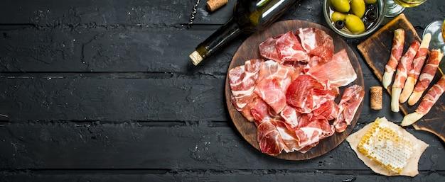 Испанская ветчина с красным вином и хлебными палочками.