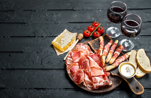 Spanish ham with red wine and breadsticks. on black rustic.