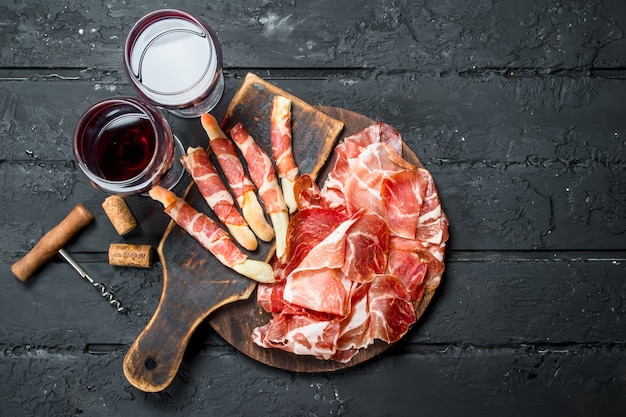 Spanish ham with red wine and breadsticks.