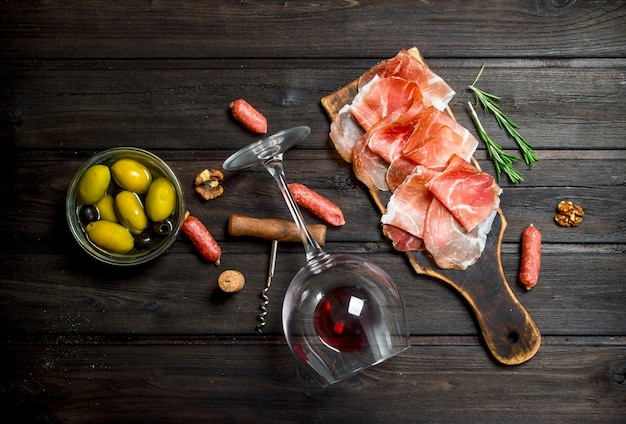 Spanish ham with red wine and nuts. on a wooden background.