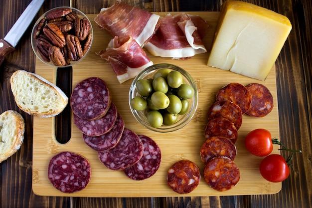 茶色の木製テーブルのまな板にスペインのハモン、ソーセージ、チーズ。上面図。
