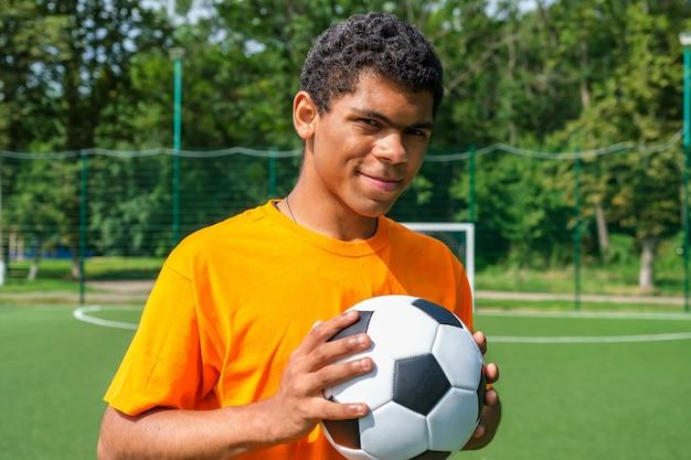 스포츠 코트에 서 있는 동안 축구 공을 들고 스페인 남자