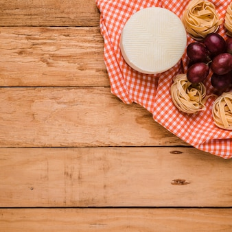 Spanish manchego cheese; red grapes and raw pasta balls over checkered table cloth on wooden desk