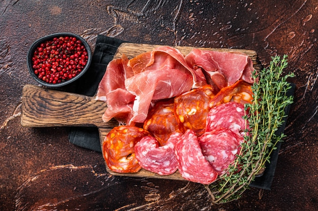 Spanish meat tapas - salami, jamon, choriso cured sausages. dark background. top view.