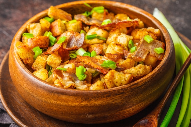 Spanish migas with pork and green onion in wooden bowl on dark background.