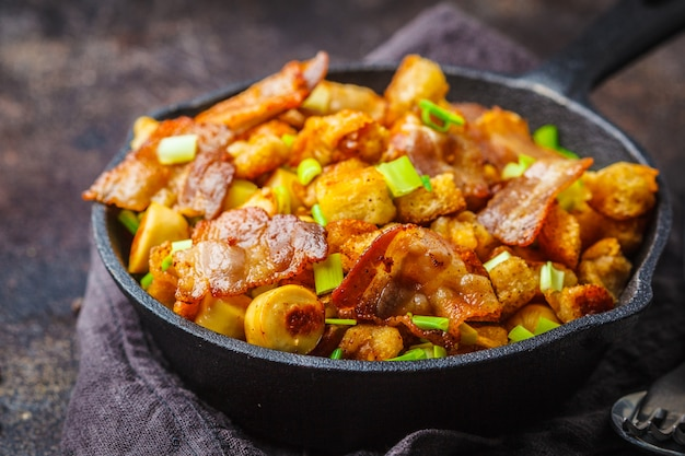 Spanish migas with pork and green onions in cast-iron pan on dark background.