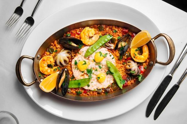 Блюдо испанской национальной кухни паэлья с морепродуктами и рисом на сковороде