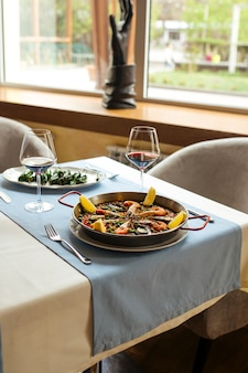 Национальная испанская паэлья из риса с морепродуктами на сковороде