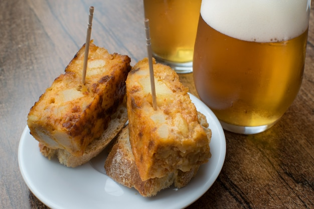 Spanish omelette appetizer and two glasses of draft beer .
