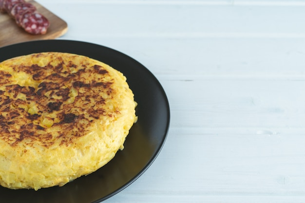 Spanish omelette on a black plate on a white wooden background.