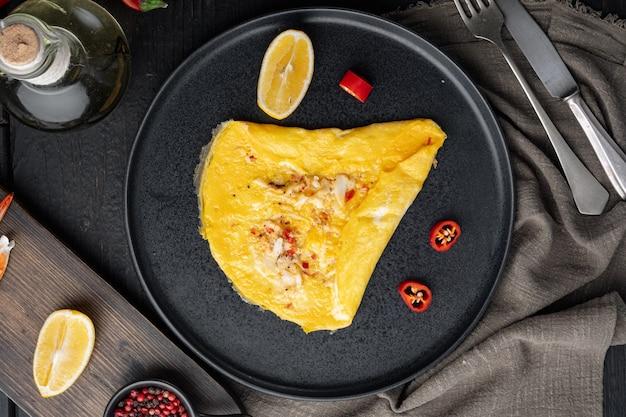 スペイン風オムレツ、新鮮な赤唐辛子、茶色と白のカニ肉、レモン、チェダーチーズ、目玉焼き、皿の上、黒い木製のテーブルの背景、上面図フラットレイ