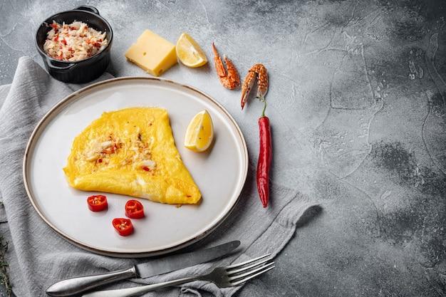 Испанский омлет, свежий красный перец чили, коричневое и белое крабовое мясо, лимон, сыр чеддер, жареные яйца, на тарелке, на сером фоне, с пространством для текста и пространством для текста