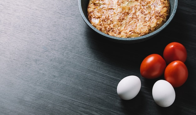 Spanish omelette on wood table, with eggs and tomatoes