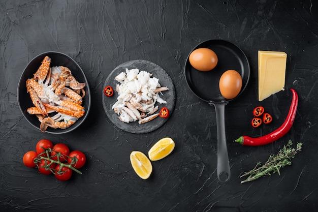スペインまたはタイのオムレツの材料、新鮮な赤唐辛子、茶色と白のカニ、レモン、チェダーチーズ、卵のセット、黒