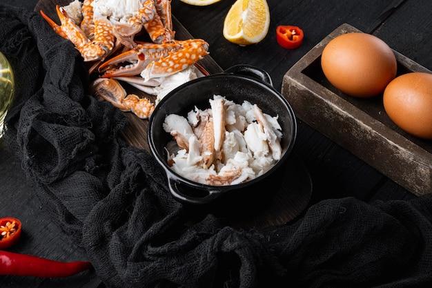 スペイン語またはタイ語のオムレツの材料、新鮮な赤唐辛子、茶色と白のカニ肉、レモン、チェダーチーズ、卵セット、黒い木製のテーブルの背景