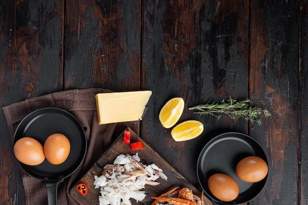 Ингредиент для испанского или тайского омлета, свежий красный перец чили, коричневое и белое крабовое мясо, лимон, сыр чеддер, набор яиц, на темном деревянном фоне, плоская планировка, вид сверху, с пространством для текста и пространством для текста