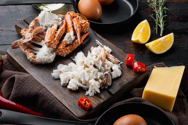スペイン語またはタイ語のオムレツの材料、新鮮な赤唐辛子、茶色と白のカニ肉、レモン、チェダーチーズ、卵セット、ダークウッドの背景