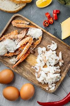 スペイン語またはタイ語のオムレツの材料、新鮮な赤唐辛子、茶色と白のカニ肉、レモン、チェダーチーズ、卵セット、灰色の背景、上面図フラットレイ